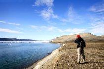 Homem de boné em pé na costa — Fotografia de Stock