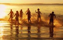 Grupo de pessoas correndo através da água — Fotografia de Stock