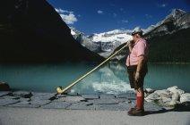 Lago Louise, Parque nacional Banff, Banff, Alberta, Canadá; Hombre tocando cuerno alpino - foto de stock