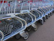 Lot of shopping carts placed in row at parking — Stock Photo