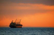 Грузовой корабль в океане на закате — стоковое фото