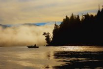 Рибалка в човні над водою — стокове фото