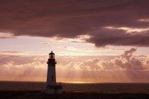 Pôr do sol ao longo do farol na costa — Fotografia de Stock