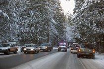 Un vehículo de emergencia hace su camino a través del tráfico pesado después de una tormenta de nieve en la capilla del Monte; Oregon, Estados Unidos de América - foto de stock