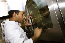 Side View Of  Chef Looking Into The Oven At Kitchen — Stock Photo
