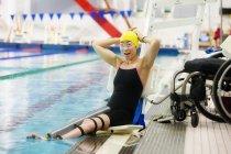 Femme paraplégique assis au bord de la piscine sur la levée et l'ajustement des lunettes — Photo de stock