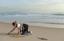 Дівчина малюнок піску — стокове фото