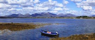 Barco en el agua contra Costa - foto de stock