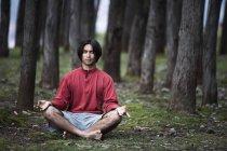 Um jovem medita e pratica Yoga em uma floresta — Fotografia de Stock