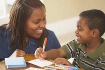 Menino feliz escrever cartões com mãe — Fotografia de Stock