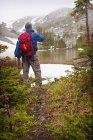 Homme de randonnée à travers montagnes — Photo de stock