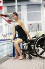 Woman in wheelchair moving onto lift at edge of swimming pool — Stock Photo