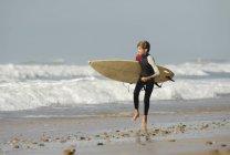 Ragazzo che funziona con il surf lungo la spiaggia — Foto stock
