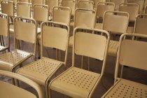 Filas de sillas de metal color beiges en el interior de - foto de stock
