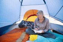 Uma jovem mulher lendo um livro dentro de uma tenda; Califórnia, Estados Unidos da América — Fotografia de Stock