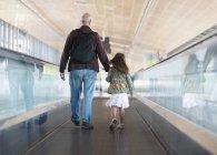 Pai e filha descer um pedway em movimento no aeroporto de Málaga; Málaga, Andalucia, Espanha — Fotografia de Stock