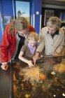Grandmother With Daughter And Granddaughter Looking At The Tidepool Display — Stock Photo