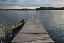 A canoe tied to a wooden dock — Stock Photo