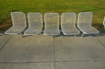 A Row Of Silver Chairs On The Cement And Grass; San Francisco, California, United States Of America — Stock Photo