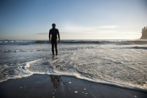 Silhouette Of A Person Standing On A Beach Looking Out Over The Ocean — Stock Photo