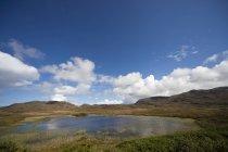 Lago rodeado por uma paisagem montanhosa — Fotografia de Stock