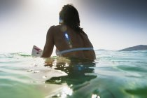 Rear view of woman sitting on surfboard in water — Stock Photo
