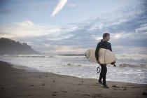 Giovane uomo con il surf, passeggiate lungo la spiaggia — Foto stock