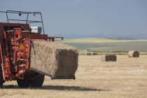 Hay Baler with Bale Coming Out — стоковое фото