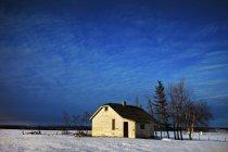 Fattoria abbandonata sulla neve coperto campo — Foto stock