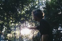 Young man reaching out to the sunlight in a forest, Little River State Park; Waterbury, Vermont, United States of America — Stock Photo