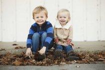 Portrait d'un jeune garçon et d'une jeune fille assis parmi les feuilles d'automne tombées — Photo de stock