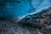 Человек смотрит на полупрозрачный голубой лед ледниковой пещеры Канвелл. Аляска, Соединенные Штаты Америки — стоковое фото
