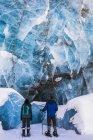 Coppia di racchette da neve esaminano grande parete blu di ghiaccio con diversi pezzi crollati di ghiaccio nella parte inferiore al capolinea del ghiacciaio Canwell. Alaska, Stati Uniti — Foto stock