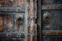 Closeup of old wooden doors with brass rings — Stock Photo