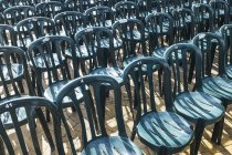 Plastic green chairs lined up in rows — Stock Photo