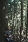 Молодой человек, стоящий в лесу с чашкой кофе, Литтл-Ривер парк государства; Уотербери, штат Вермонт, Соединенные Штаты Америки — стоковое фото
