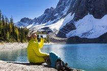 Female hiker drinking from bottle — Stock Photo