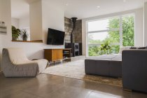 Серая ткань мягкая секционные диван и кремового цвета сидели стулья в гостиной внутри современного куб стиль дома; Квебек, Канада — стоковое фото