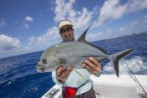 Fisherman on boat holding fresh caught Jackfish — Stock Photo