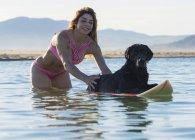Woman having fun with her pet dog in the water; Tarifa, Cadiz, Costa de la Luz, Andalusia, Spain — Stock Photo