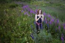 Femme faire du yoga dans une prairie de fleurs sauvages — Photo de stock