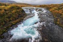 Cascada y agua corriente en un río - foto de stock