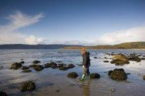 Escocia; Mujer caminando a través de piscinas de marea baja en la playa - foto de stock