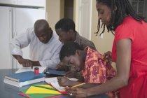 Afrikanische amerikanische Eltern ihren Kindern bei den Hausaufgaben helfen — Stockfoto