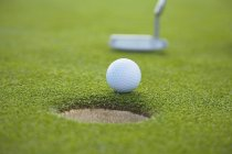 Cloesup of ball, hole and club on golf course — Stock Photo