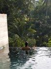 Вид сзади на женщину в бассейне. Бали Индонезия ; — стоковое фото