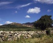 Steinmauer vor Bergen — Stockfoto