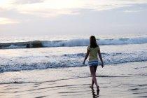 Ragazza adolescente che cammina sulla spiaggia — Foto stock