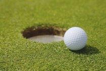 Golf Ball Near Hole — Stock Photo