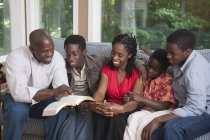 Christian african american family reading bible toogether at home — Stock Photo